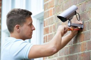 depositphotos 76066841 stock photo security consultant fitting security camera